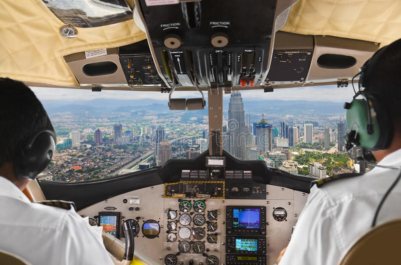 Pilots in the plane cockpit and city. Pilots in the plane cockpit and town royalty free stock photos