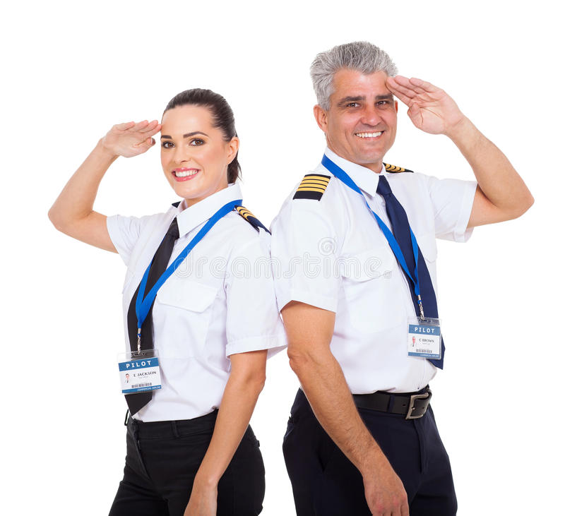 Pilots saluting. Beautiful female first officer and senior captain pilots saluting over white background stock photo