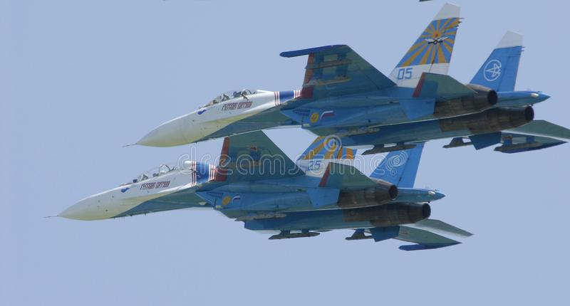 Pilots of two military aircraft SU27 jointly perform a turn. royalty free stock photo