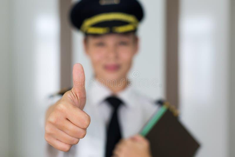 Pilotstående för yrkesmässig kvinna som ger upp tummarna arkivfoton