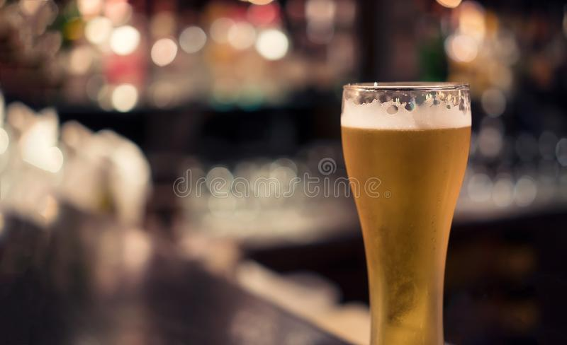 Pilsner beer glass with bar background. And bokeh royalty free stock photography