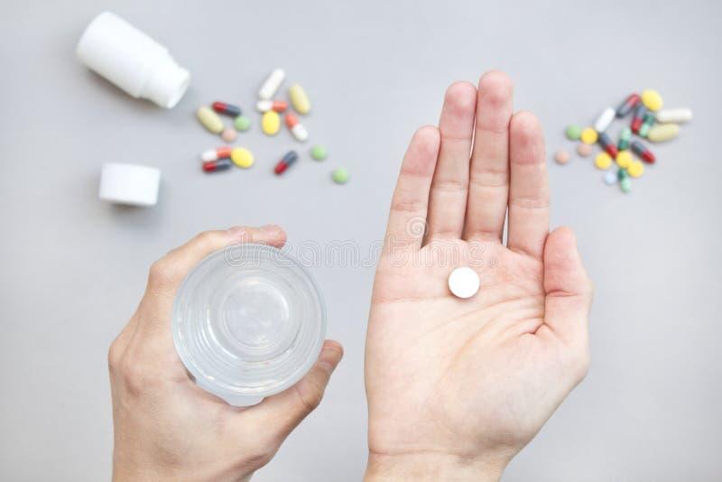 Pilule blanche et un verre de l'eau dans des mains de l'homme Concept de santé photos libres de droits