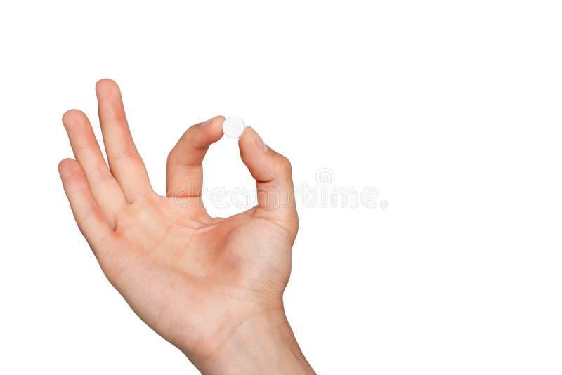 Pilule dans la main du ` s de l'homme sur le fond blanc images libres de droits