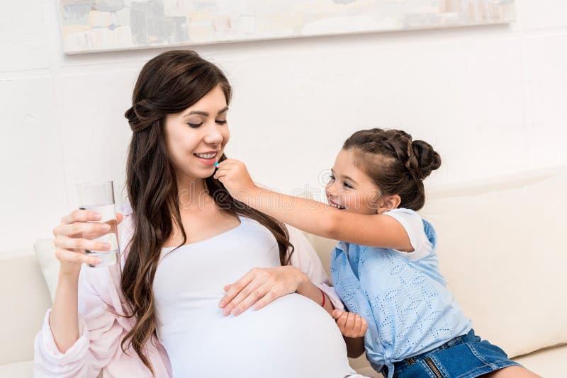Pilule de alimentation de fille à la mère photographie stock
