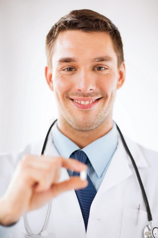 Pilule de offre de jeune docteur masculin image stock