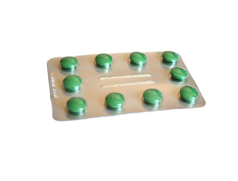 Pilules à l'arrière-plan vert de blanc de habillage transparent image libre de droits