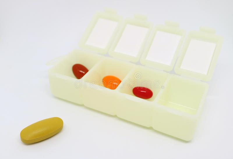 Pilules assorties de supplément dans l'organisateur quotidien Case de pilule avec l'un d'entre eux à l'extérieur photo libre de droits