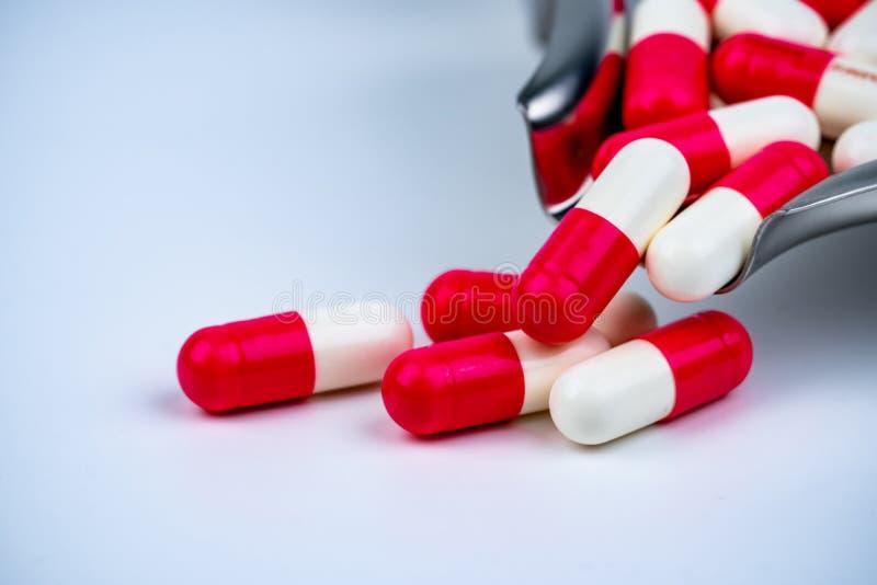 pilules blanc rouge de capsule sur le plateau de drogue d'acier inoxydable et quelque sur la table blanche Fond de pharmacie de p photos stock