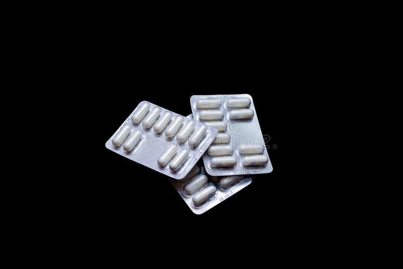 Pilules blanches dans les paquets argent?s sur un fond noir, isolat, l'espace de copie photos libres de droits