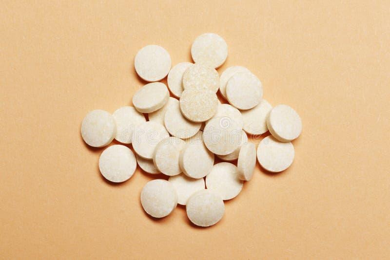 Pilules blanches sur un fond rose photographie stock