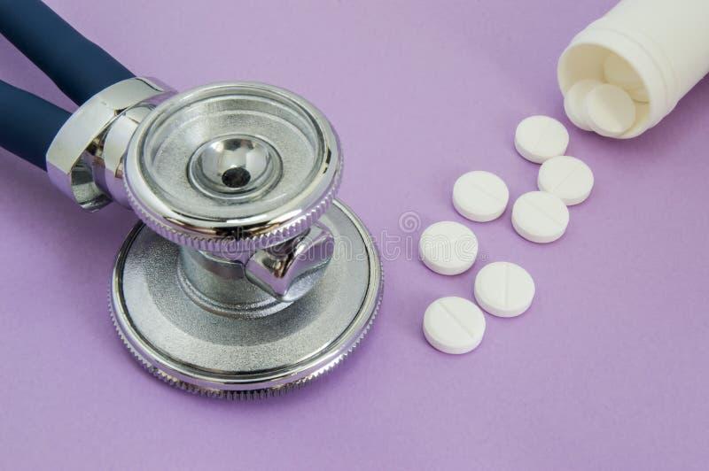 Pilules blanches tombant hors d'un tube ou un pot en plastique et la tête du stéthoscope sur un fond pourpre Vue ou photo pour à  photo libre de droits