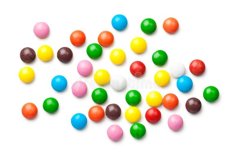Pilules colorées de bonbons au chocolat d'isolement sur le fond blanc images libres de droits