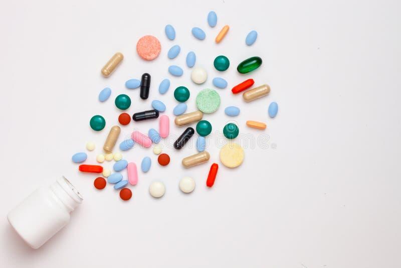 Pilules, comprimés assortis et capsules pharmaceutiques de médecine sortant du récipient au-dessus du fond blanc image libre de droits