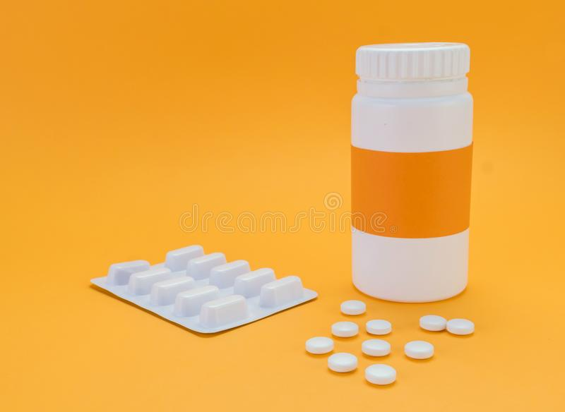 Pilules débordant une bouteille ouverte sur le fond orange photo libre de droits