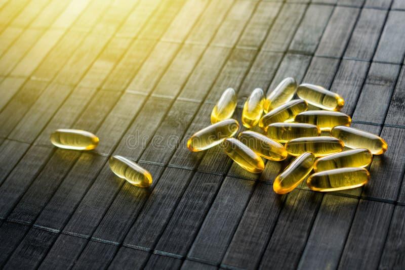 Pilules d'or de protection solaire sur le fond en bois noir au soleil Les suppléments diététiques protègent la peau contre le sol photo stock