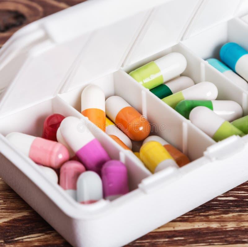Pilules de différentes couleurs dans une boîte photo stock