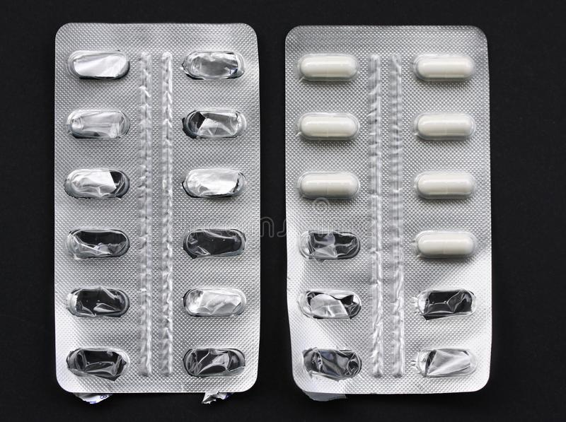 Pilules de médecine dans des pilules de paquets dans les capsules en aluminium de habillage transparent Un certain nouveau et un  photographie stock