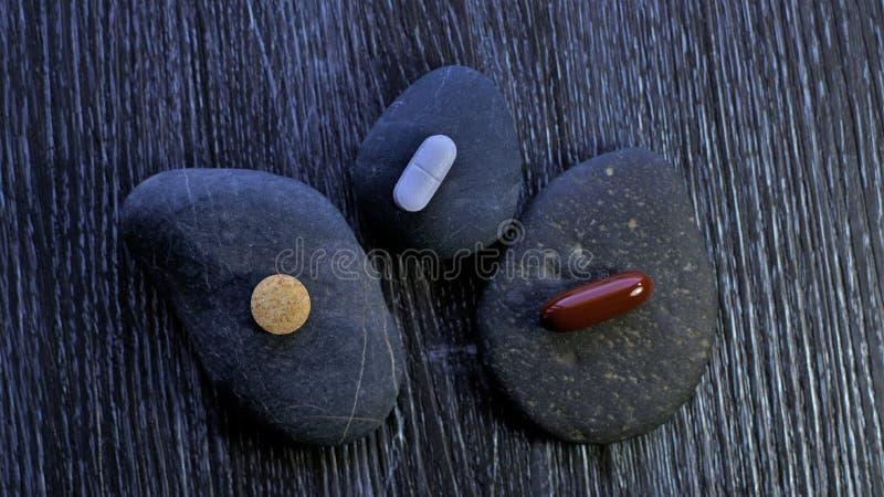 Pilules de médecine ou pilules de drogue sur des pierres de caillou photos stock