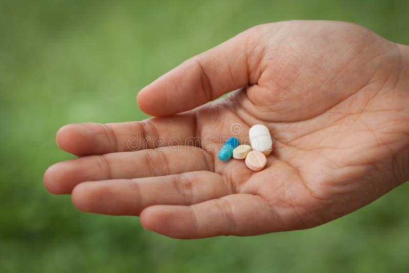Pilules de plan rapproché sur la main de femme image stock