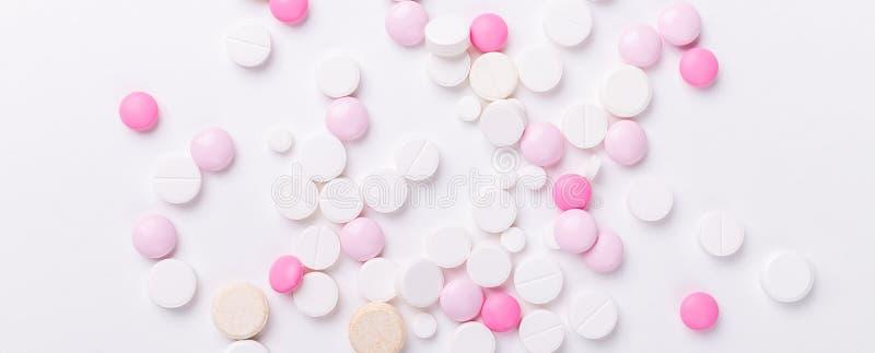 Pilules de rose et blanches sur le fond blanc Tas de divers comprimés et pilules assortis de médecine Banni?re horizontale photo stock