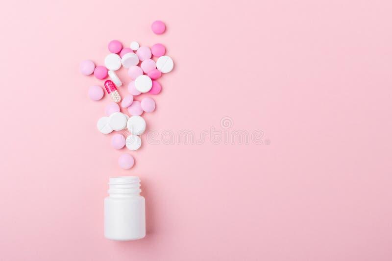 Pilules de rose et blanches sur le tas en plastique de bouteille de fond rose de divers comprimés et pilules assortis de médecine image libre de droits