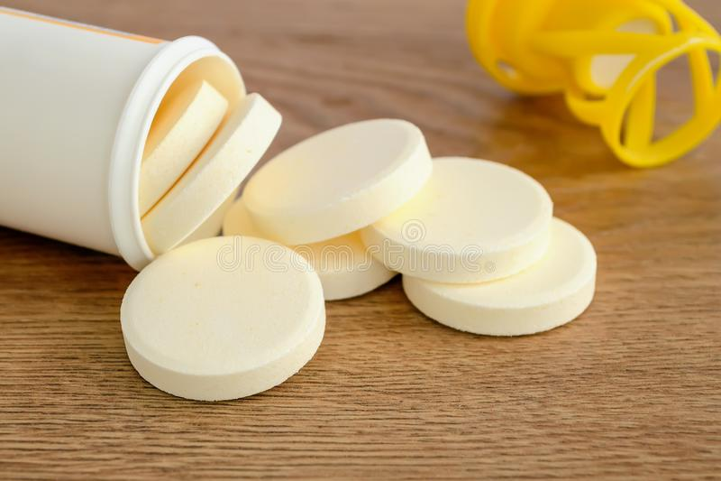 Pilules effervescentes solubles de vitamine renversées hors d'une bouteille en plastique sur un fond en bois Vitamines et suppl?m photographie stock