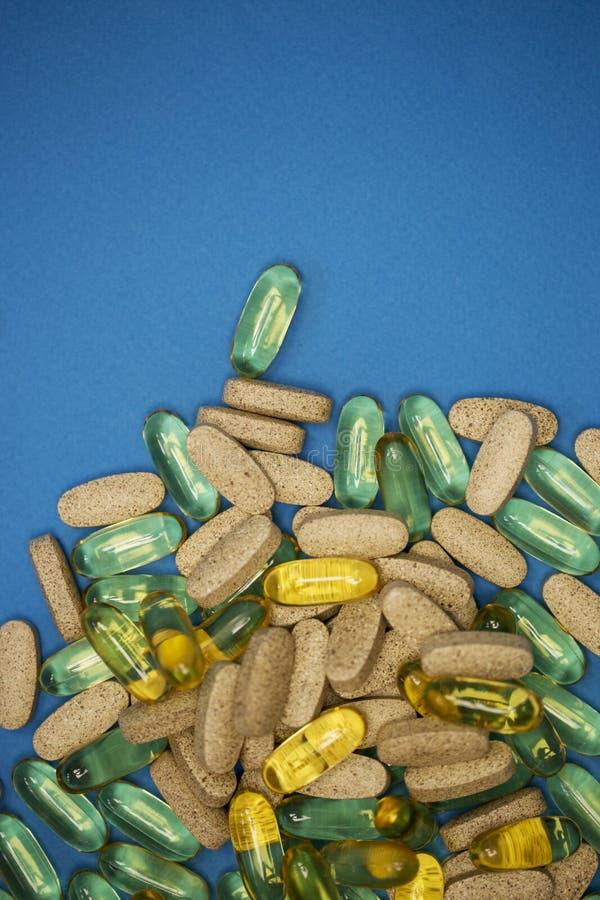 Pilules et médecines dispersées sur le fond bleu photos libres de droits