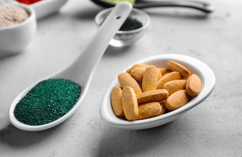 Pilules et spirulina de poudre de Camu dans la vaisselle de cuisine photos stock