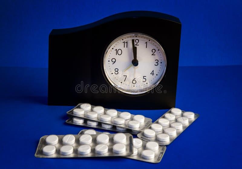 Pilules et une horloge photos libres de droits