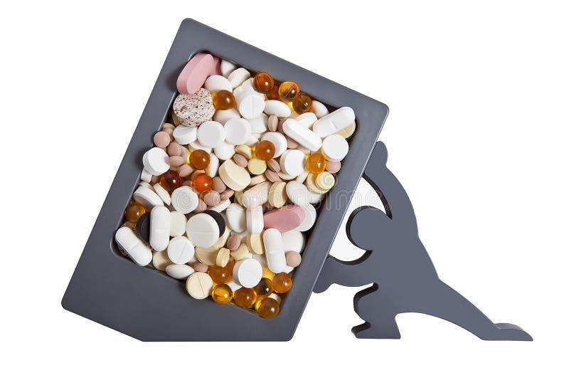 Pilules et vitamines dans un récipient en plastique, soutenu par le chiffre d'un homme photos stock