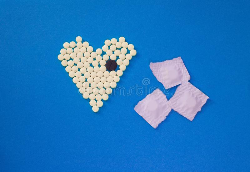 Pilules jaunes dans la forme du coeur avec le grand comprimé noir image libre de droits
