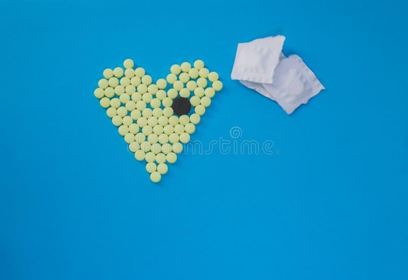 Pilules jaunes dans la forme du coeur avec le grand comprimé noir photo stock