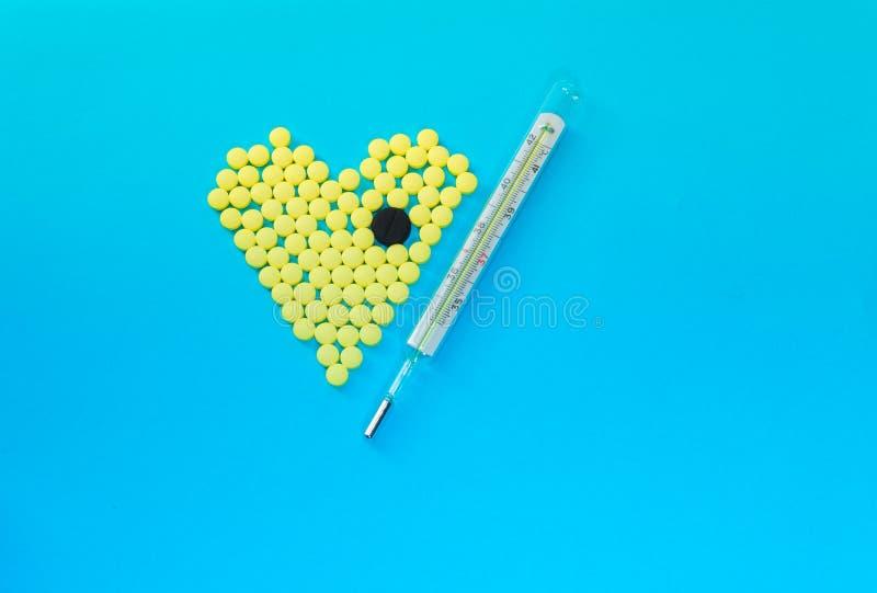 Pilules jaunes dans la forme du coeur avec le grand comprimé noir et le thermomètre médical image stock