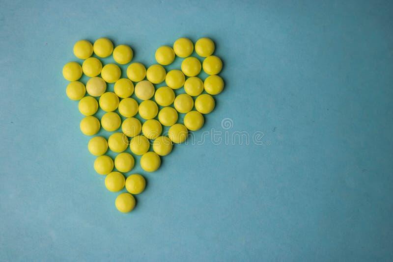 Pilules jaunes de petit rond pharmaceptic médical, vitamines, drogues, antibiotiques sous forme de coeur sur un fond bleu, textur photographie stock