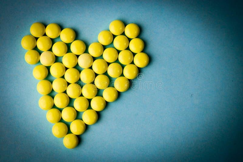 Pilules jaunes de petit rond pharmaceptic médical, vitamines, drogues, antibiotiques sous forme de coeur sur un fond bleu, textur image libre de droits