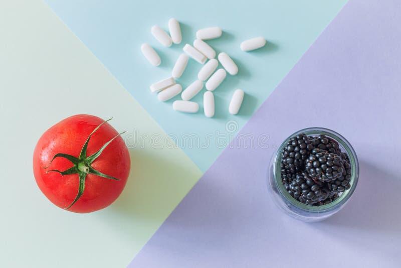 Pilules médicales et fruit frais et sain une source des vitamines naturelles photo stock