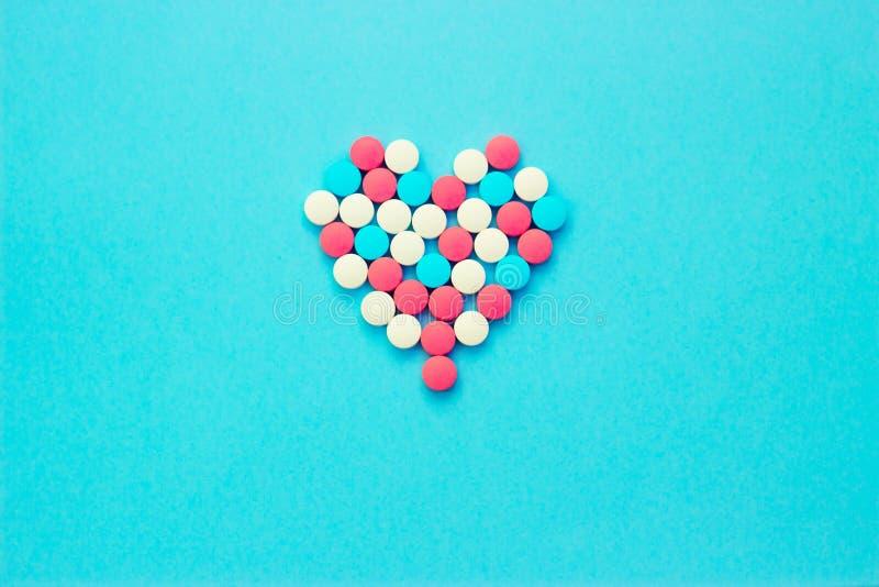 Pilules multicolores des pots blancs sur un fond bleu photo stock