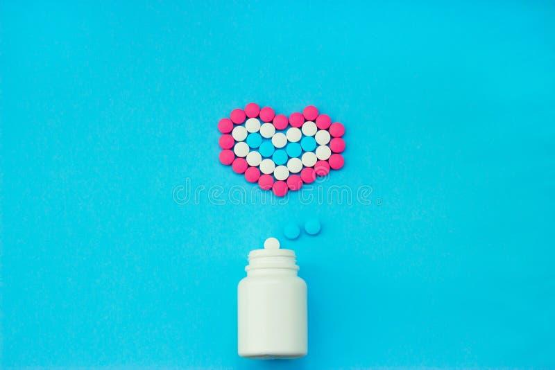 Pilules multicolores des pots blancs sur un fond bleu photographie stock libre de droits