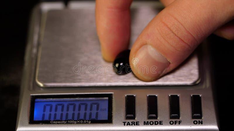 Pilules noires de mesure de poids Pèse le macro de comprimé Le docteur mesure des pilules de poids en gros plan photos stock