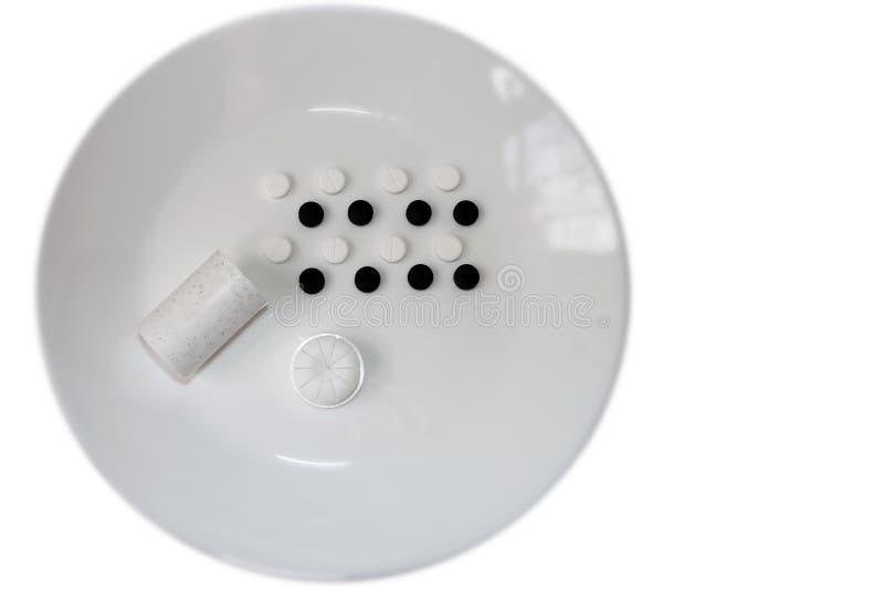 Pilules noires et blanches d'un plat image stock