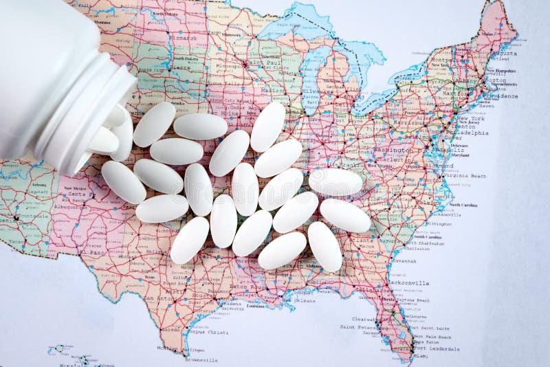 Pilules pharmaceutiques blanches débordant la bouteille de prescription au-dessus de la carte du fond de l'Amérique image stock