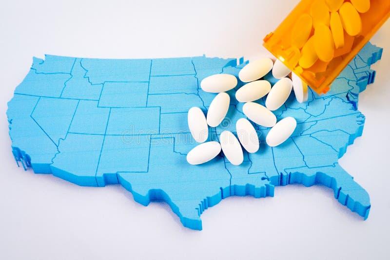 Pilules pharmaceutiques blanches débordant la bouteille de prescription au-dessus de la carte du fond de l'Amérique image libre de droits