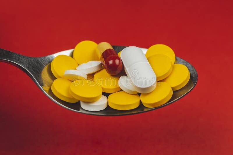 Pilules pharmaceutiques de médecine, sur la cuillère sur le fond rouge image libre de droits