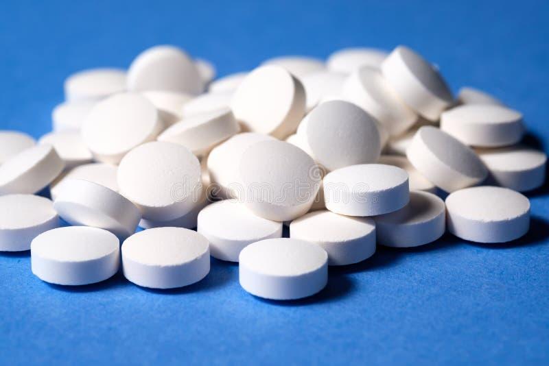 Pilules pharmaceutiques rondes blanches sur le fond bleu photo stock