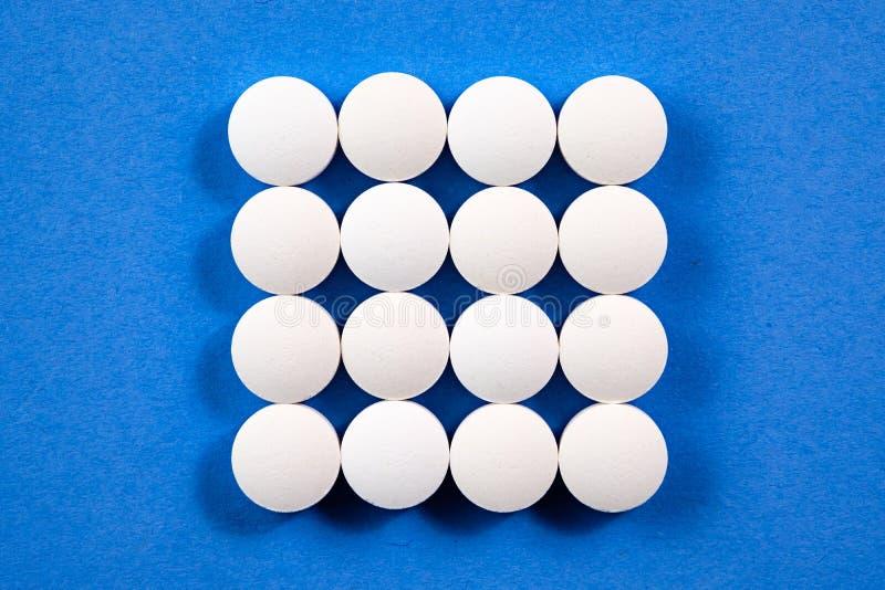 Pilules pharmaceutiques rondes blanches sur le fond bleu photo libre de droits