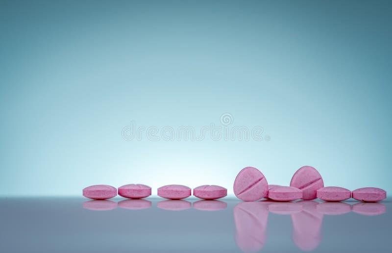 Pilules roses de comprimés avec l'ombre sur le fond de gradient Industrie pharmaceutique Produits de pharmacie Vitamines et suppl photographie stock