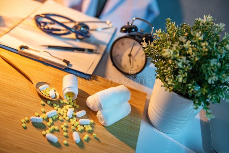 Pilules se renversant hors des bouteilles de pilule sur le bureau de docteur photo stock