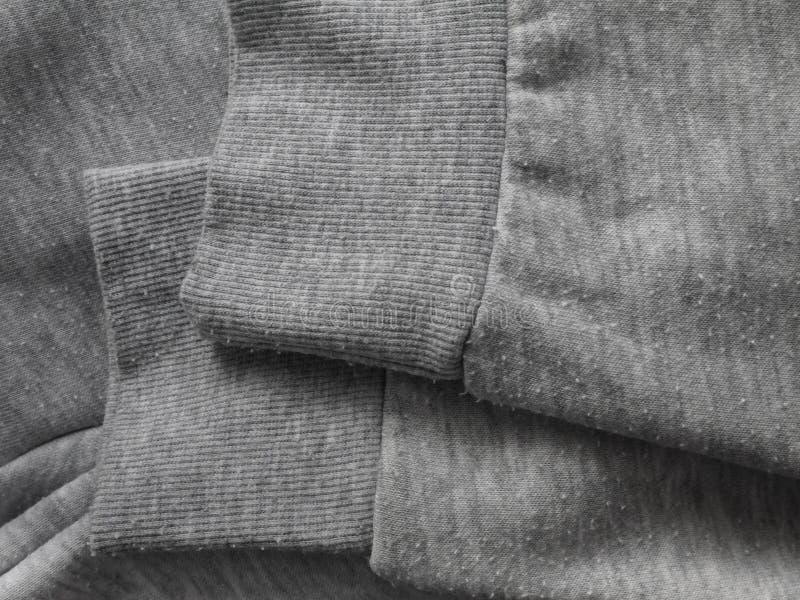 Pilules sur le tissu gris de pull molletonné de bruyère photo stock