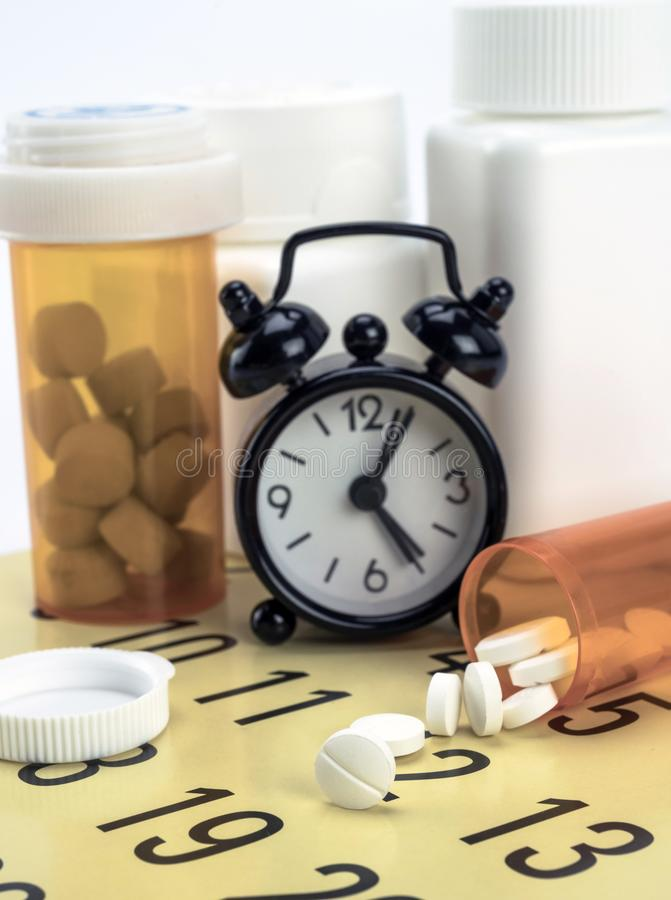 Pilules sur un calendrier à côté d'une horloge images libres de droits