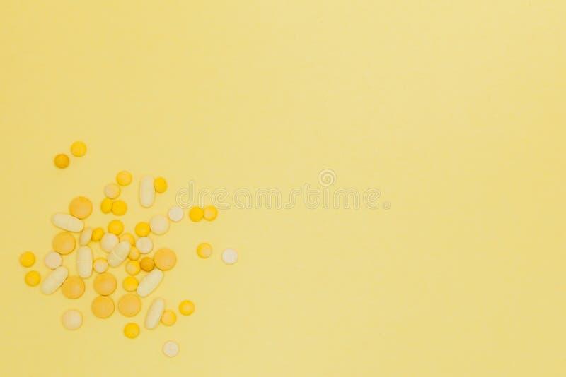 Pilules sur un fond jaune Concept de construction Pilules d'un soleil insolation Fond des maladies d'été Copiez l'espace photographie stock libre de droits